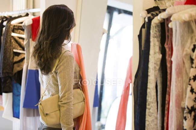 Jovem mulher escolhendo roupas em boutique — Fotografia de Stock