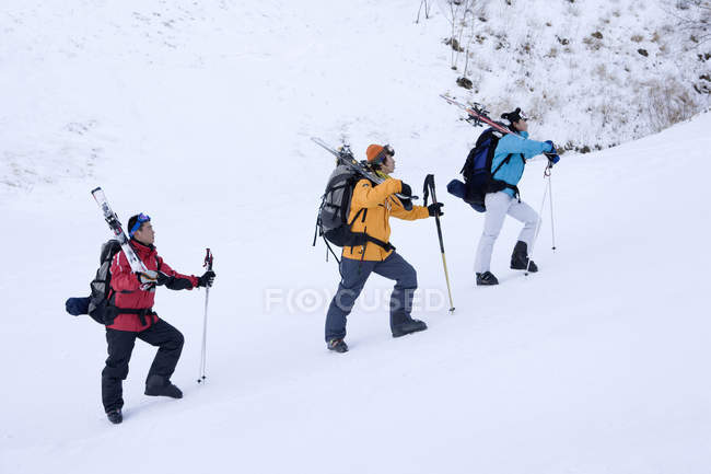 Three Chinese skiers hiking in snow-capped mountains — Stock Photo