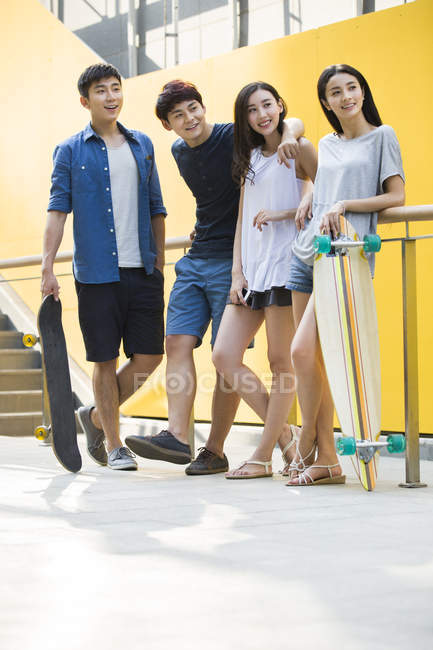Chinese friends standing with skateboards on street — Stock Photo