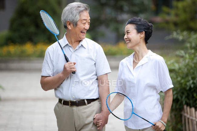 Senior Chinese couple walking in residential district with badminton rackets — Stock Photo