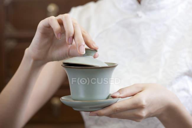 Жінка в традиційних cheongsam проведення чашка чаю — стокове фото