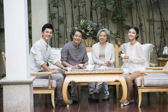 Chinese family sitting with tea and looking in camera — Stock Photo
