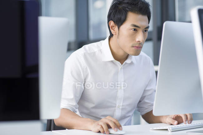 Chinese businessman using computer in office — Stock Photo