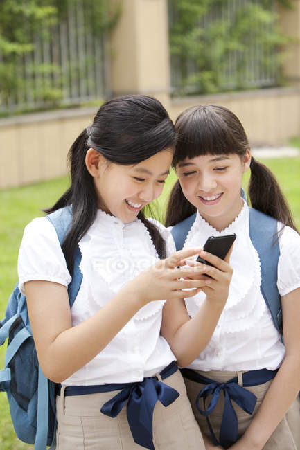 Chinese schoolgirls using smartphone in school yard — Stock Photo