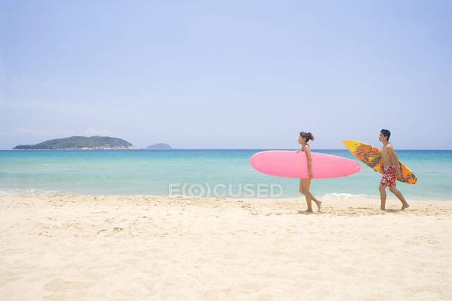 Chinese couple with surfboards walking on beach in China — Stock Photo