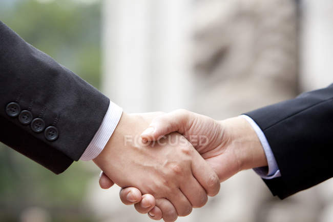 Close-up of businessmen handshake on street — Stock Photo