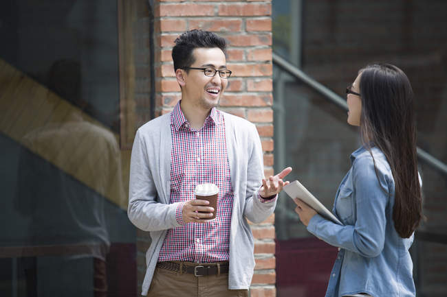 Chinese colleagues talking on street — Stock Photo