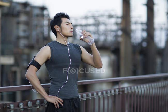Homem chinês descansando após exercitar-se na rua e bebendo água — Fotografia de Stock