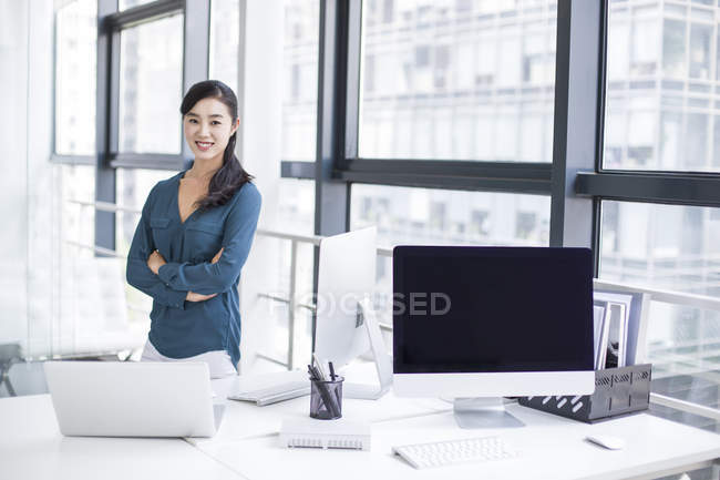 Chinese businesswoman at workplace looking in camera — Stock Photo