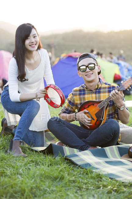 Chinese couple playing musical instruments at camping — Stock Photo