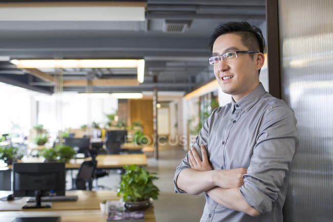 Chinese man standing in office with arms folded — Stock Photo