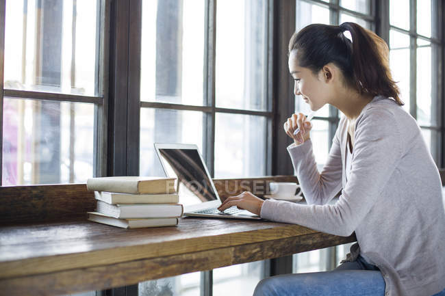 Chinese woman studying with laptop in cafe — Stock Photo