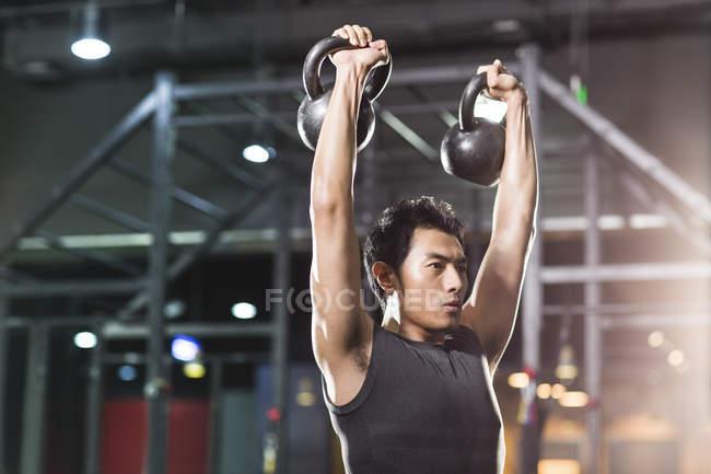 Chinesischer Mann Training mit Kettlebells in Crossfit gym — Stockfoto