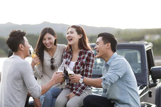 Amigos chineses sentados no carro com cerveja — Fotografia de Stock