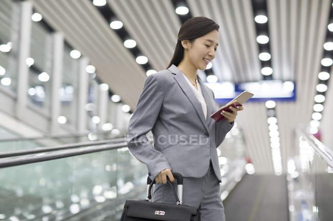 Китайская предпринимательница использует смартфон на эскалаторе — стоковое фото