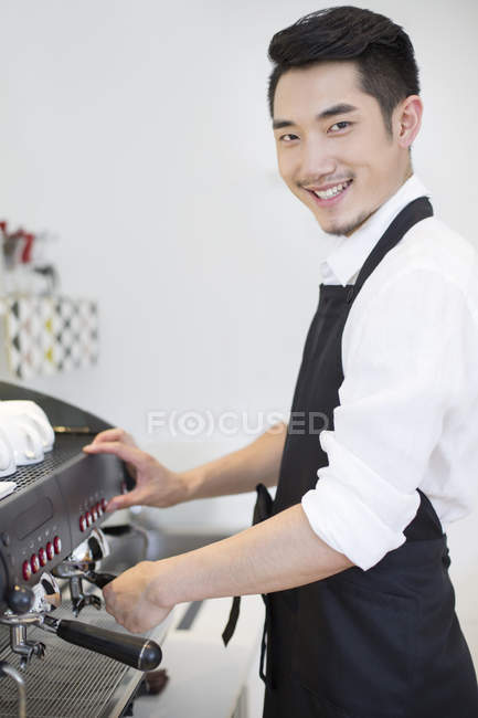 Chinese barista standing at coffee maker and looking in camera — Stock Photo