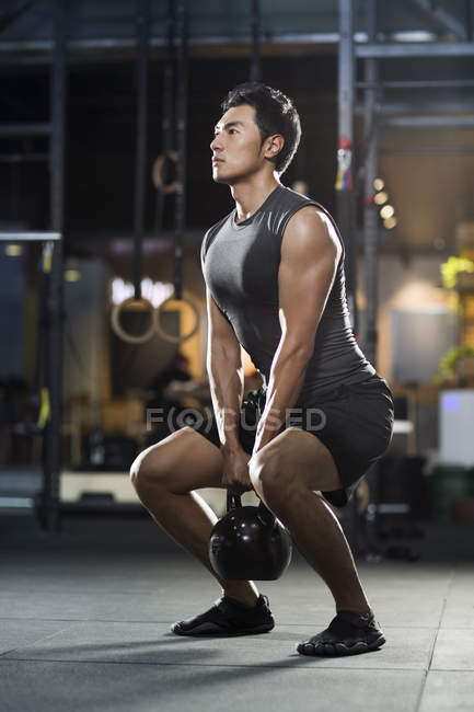 Chinesischer Mann Training mit Kettlebell in Crossfit gym — Stockfoto