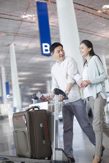 Mature chinese couple walking in airport with suitcase — Stock Photo