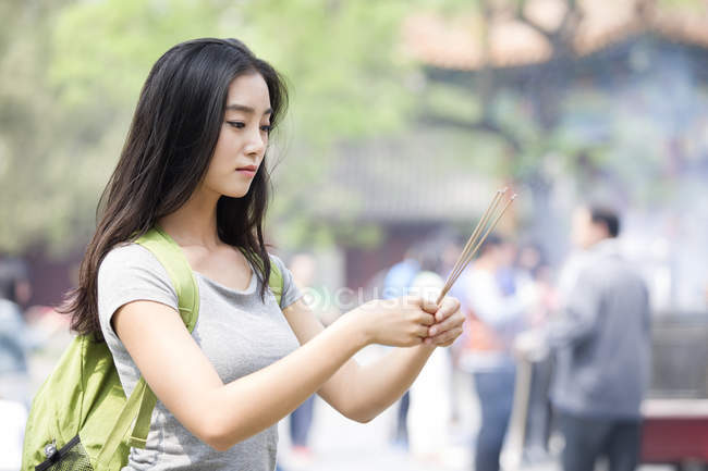 Chinese woman burning incense in Lama Temple — Stock Photo