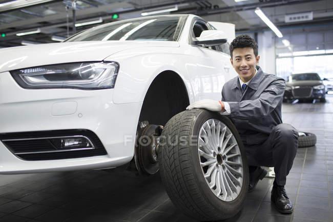 Garagiste chinois tenant la roue de voiture en atelier — Photo de stock