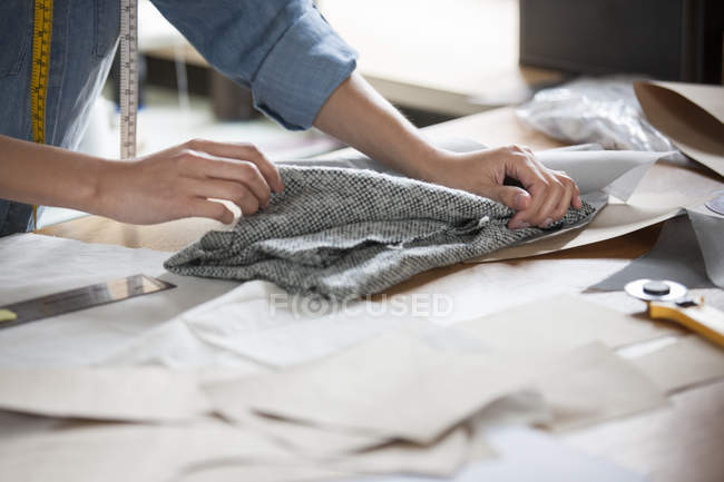 Cropped view of female tailor working in studio with textile — Stock Photo