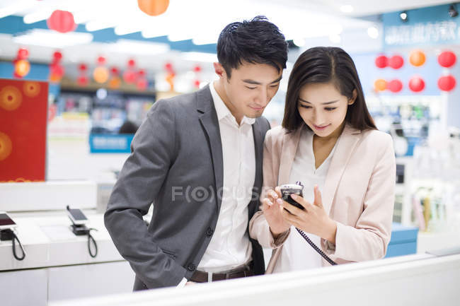 Chinese couple looking at smartphone in electronics store — Stock Photo
