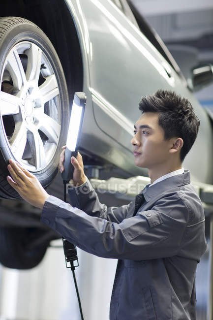 Chinese auto mechanic examining car with flashlight — Stock Photo