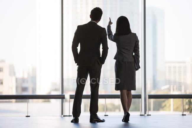Hommes d'affaires regardant par la fenêtre dans un immeuble de bureaux, vue arrière — Photo de stock