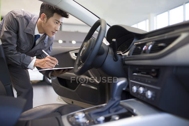 Chinese auto mechanic making notes in car — Stock Photo