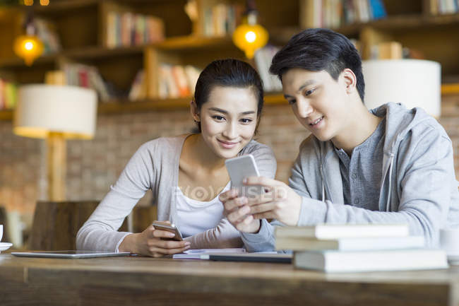 Chinese students using smartphone in cafe — Stock Photo