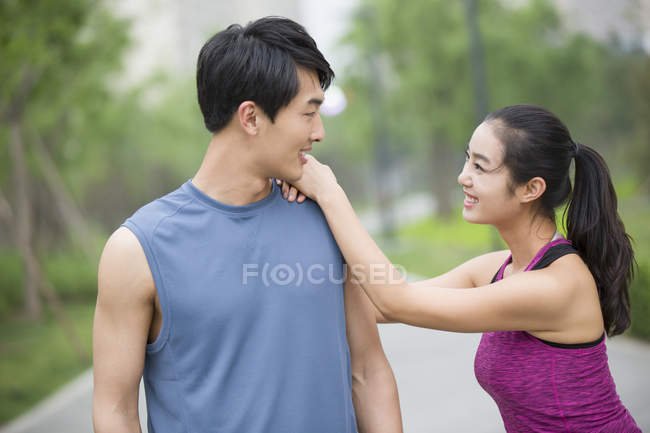 Chinese couple of joggers taking break and talking — Stock Photo