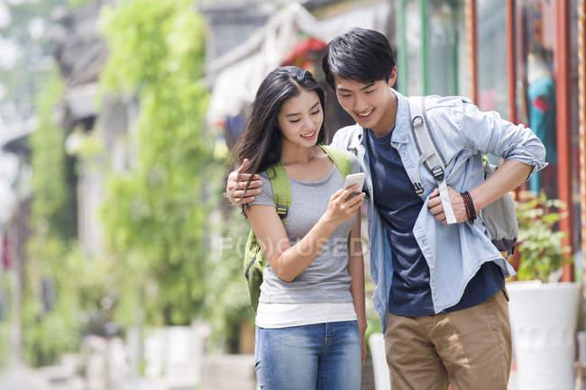 Chinese couple using smartphone on street of Beijing — Stock Photo