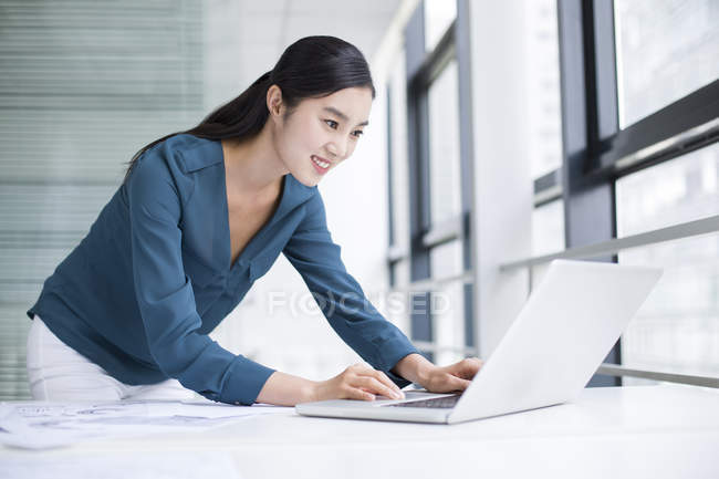 Chinese businesswoman using laptop in office — Stock Photo