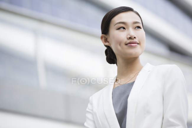Chinese businesswoman looking at view and smiling — Stock Photo