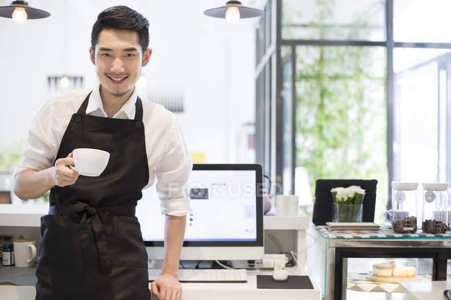 Chinese coffee shop owner at counter with cup of coffee — Stock Photo