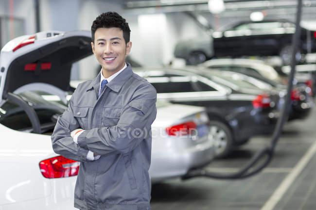 Automóvel mecânico chinês em pé na oficina com os braços dobrados — Fotografia de Stock
