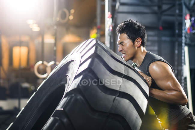 Chinese man pushing large tire in crossfit gym — Stock Photo