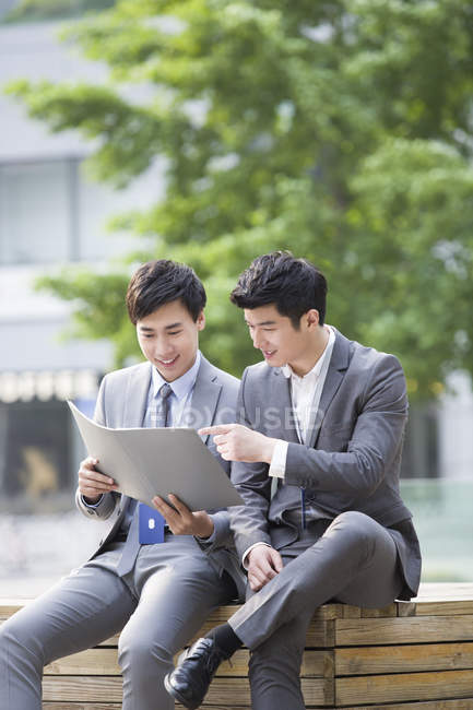Chinese businessmen working with documents on street — Stock Photo