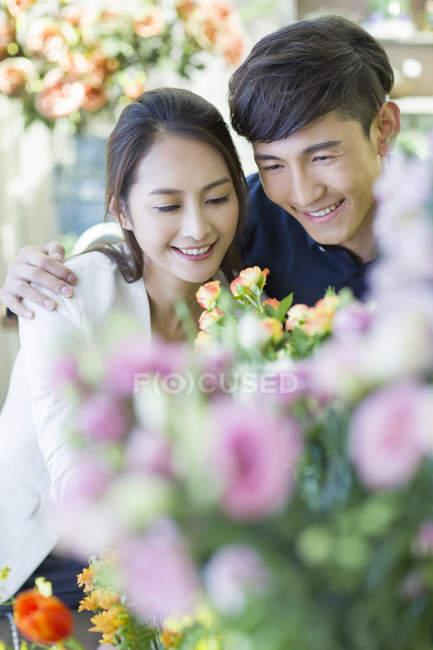 Coppia cinese che sceglie fiori in negozio — Foto stock