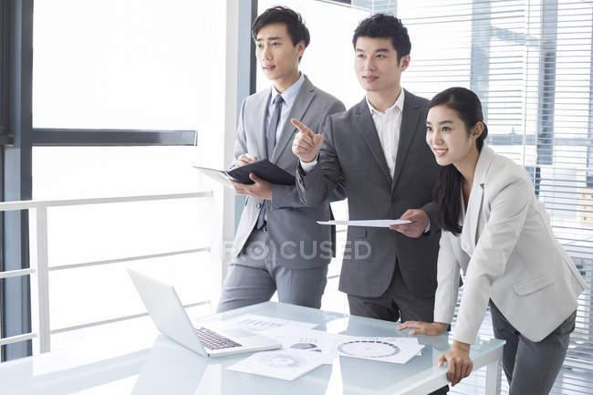 Les hommes d'affaires chinois pointant vers réunion dans la salle de conseil — Photo de stock