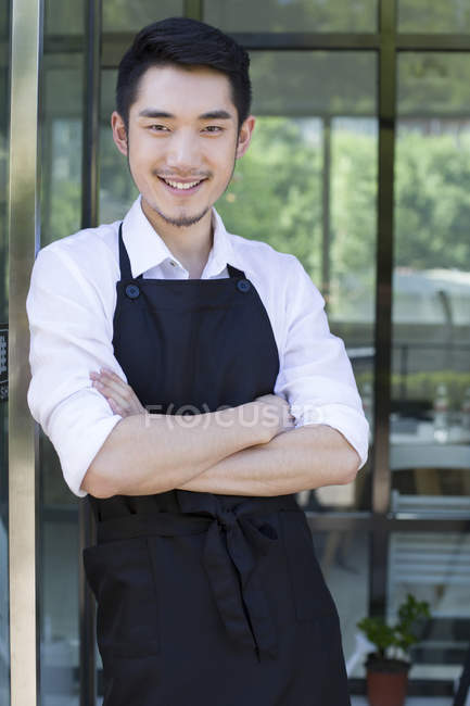 Shopkeeper standing in doorway of coffee shop with arms folded — Stock Photo
