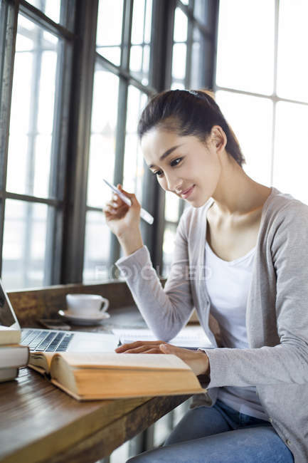 Chinese female student studying in cafe with book — Stock Photo