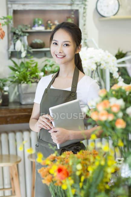 Китайский флорист держит цифровой планшет в магазине — стоковое фото