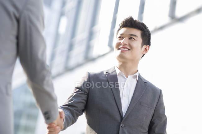 Uomini d'affari cinesi che stringono la mano sulla strada — Foto stock