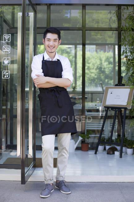 Крамаря стояв у дверях кафе з склавши руки — стокове фото