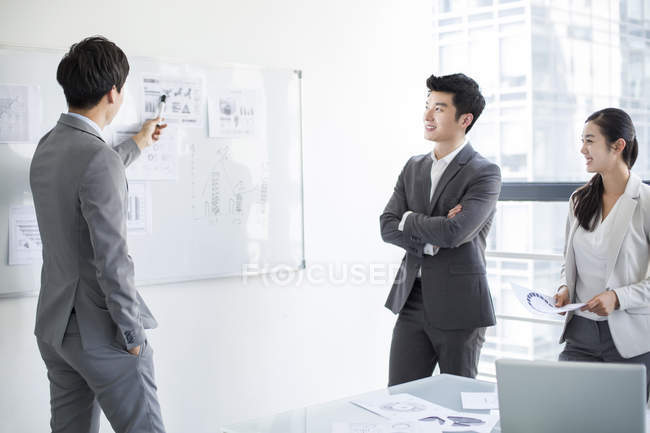 Chinese business people talking at whiteboard in meeting room — Stock Photo