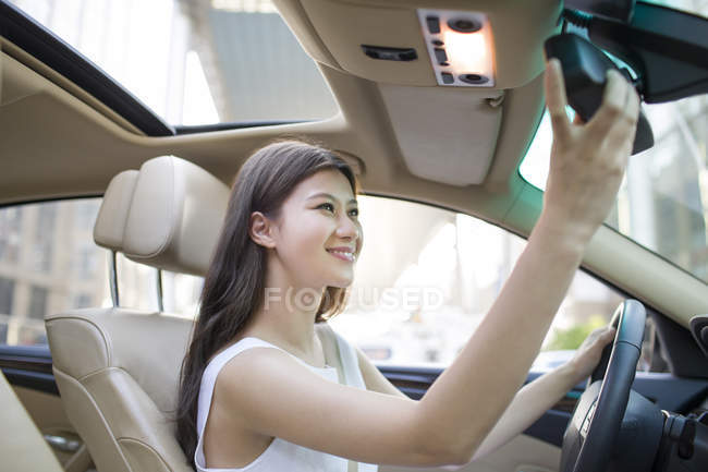 Chinese woman adjusting mirror in car — Stock Photo