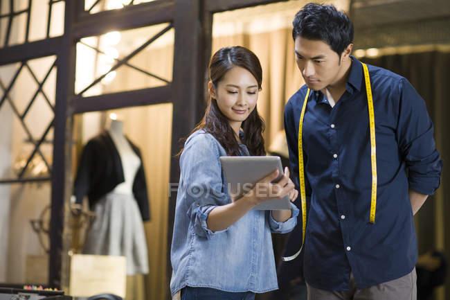Créateurs de mode chinois utilisant tablette numérique en atelier — Photo de stock