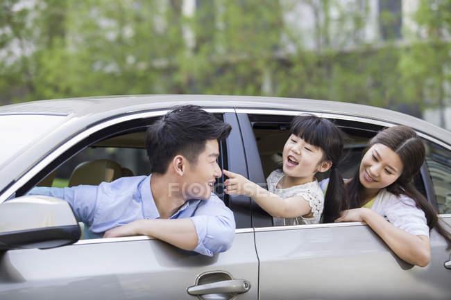 Chinesische Familie reitet und lehnt sich aus Auto — Stockfoto