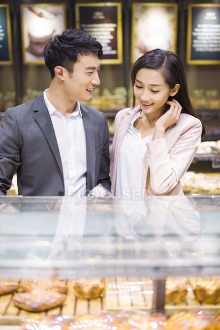 Casal chinês escolhendo pastelaria padaria — Fotografia de Stock